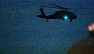 An Idaho National Guard helicopter lifts off from a crash site where another Guard helicopter was reported to have crashed south of Gowen Field in Boise Thursday Nov. 6, 2014 sometime after 7 p.m. There was no immediate word on injuries. (AP Photo/The Idaho Statesman, Darin Oswald)