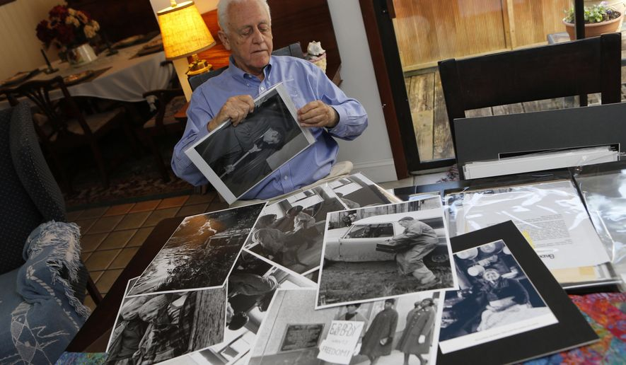 In this photo taken on Oct. 27, 2014, photographer Bruce Roberts sorts through images he's taken over the years at his home in Morehead City, N.C. During his career as a photojournalist, Roberts worked as the director of photography and the senior photographer at Southern Living, as a photographer for The Charlotte Observer during the civil rights movement and freelanced for publications like Sports Illustrated, Time and Life magazines. (AP Photo/The Jacksonville Daily News, John Althouse)
