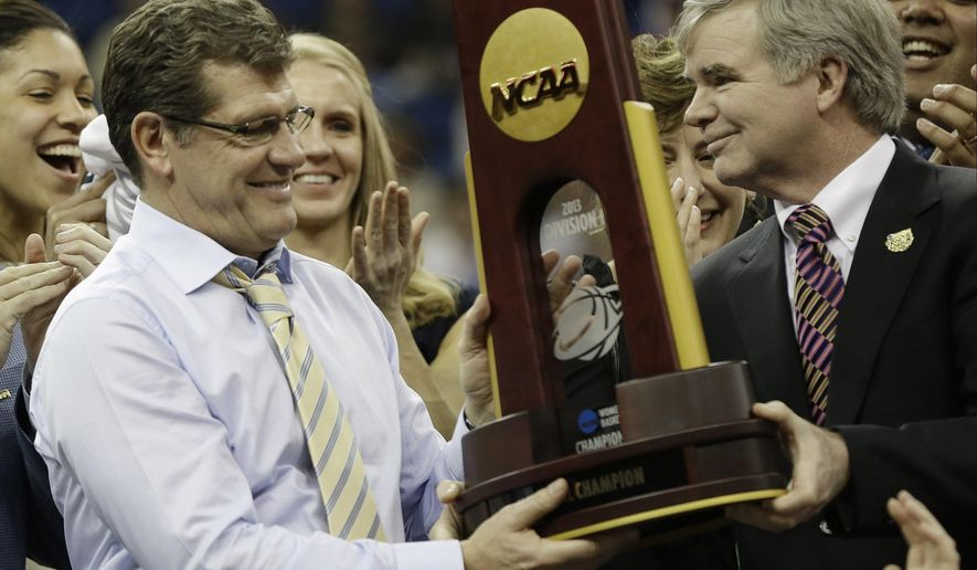 FILE - In this April 9, 2013 file photo, Connecticut head coach Geno Auriemma receives the championship trophy from NCAA president Mark Emmert, right, after defeating Louisville at the women's Final Four NCAA college basketball tournament in New Orleans. Auriemma and the UConn Huskies enter the season as two-time defending champions and have won 46 straight games.  (AP Photo/Dave Martin, File)