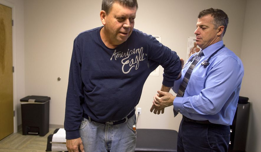 ADVANCE FOR USE SUNDAY, NOV. 9 - In this photo taken on Thursday, Oct. 30, 2014, Dr. Douglas Farrago assists Roy Coleman during a physical therapy session for shoulder pain at Forest Direct Primary Care in Forest, Va. (AP Photo/News & Daily Advance, Autumn Parry)