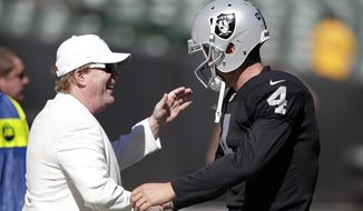 Oakland Raiders owner Mark Davis, left, shakes hands with quarterback Derek Carr (4) before an NFL football game against the San Diego Chargers in Oakland, Calif., Sunday, Oct. 12, 2014. (AP Photo/Marcio Jose Sanchez)