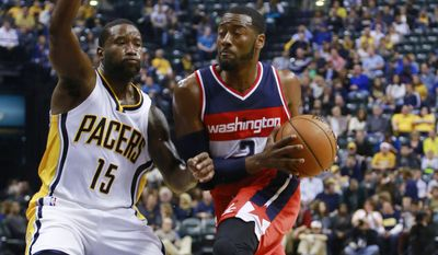 Washington Wizards guard John Wall, right, moves to the basket as Indiana Pacers guard Donald Sloan defends during the first half of an NBA basketball game in Indianapolis, Saturday, Nov. 8, 2014.  (AP Photo/R Brent Smith)