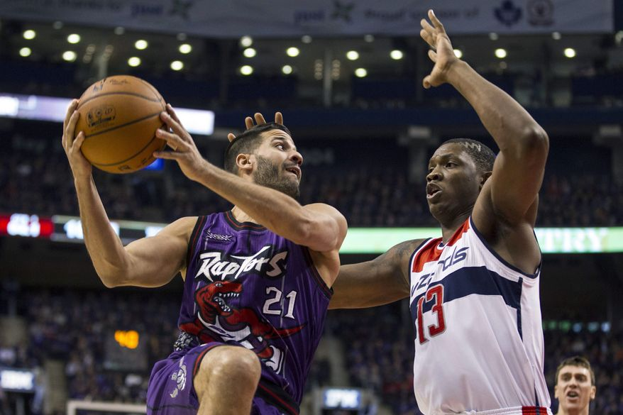 Toronto Raptors' Greivis Vasquez, left, looks to pass against Washington Wizards' Kevin Seraphin during the first half of an NBA basketball game Friday, Nov. 7, 2014, in Toronto. (AP Photo/The Canadian Press, Chris Young)