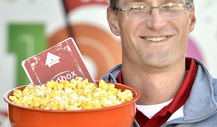 ADVANCE FOR RELEASE SUNDAY, NOV. 9, 2014, AT 12:01 A.M. CST - In this Wednesday, Oct. 29, 2014 photo, Steve Huisenga, vice-president of sales for Jolly Time Pop Corn, poses with a bowl of Jolly Time Blast O Butter popcorn and a Redbox movie, at Jolly Time Pop Corn's Sioux City, Iowa headquarters. Huisenga and Redbox vice-president of digital marketing, Mike Wokosin, have teamed together for a promotion that gives prospective University of Iowa business school students a bag of Jolly Time popcorn and a Redbox gift card. The two are both graduates of the business school. (AP Photo/The Sioux City Journal, Tim Hynds)