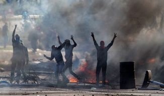 Arab-Israelis flash victory signs during a protest of the fatal shooting of a 22-year-old Arab-Israeli who appeared in video footage to be retreating from police. Thousands of Arabs took to the streets Saturday to protest the shooting, with many hurling rocks and firebombs. (Associated Press)