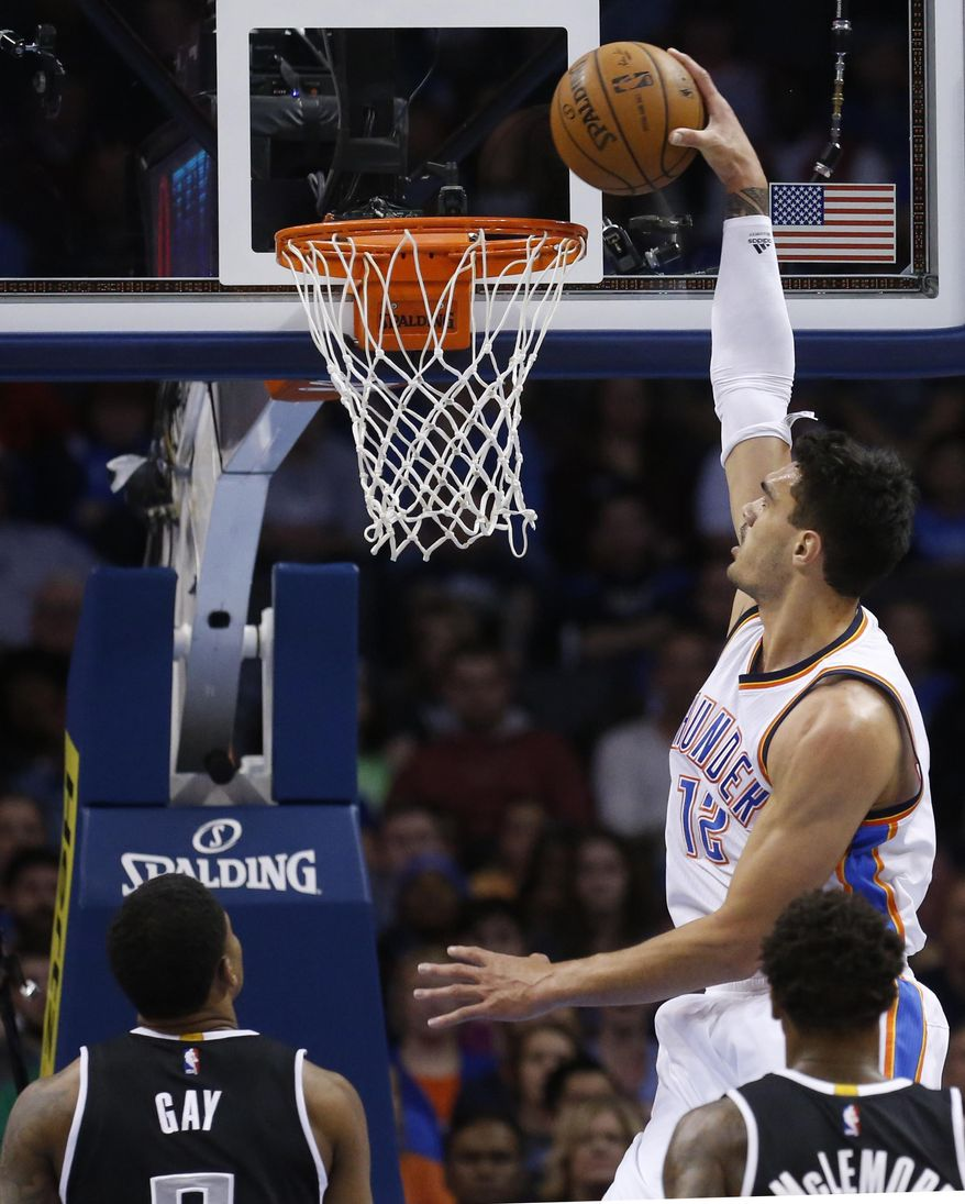 Oklahoma City Thunder center Steven Adams (12) goes up for a dunk in front of Sacramento Kings forward Rudy Gay (8) and guard Ben McLemore, front, in the first quarter of an NBA basketball game in Oklahoma City, Sunday, Nov. 9, 2014. (AP Photo/Sue Ogrocki)