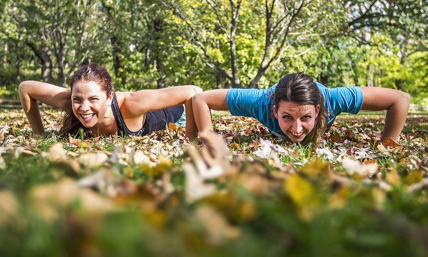 In this Oct. 7, 2014 photo, Katie Arnold, left, of Crystal Lake, Ill., and Samantha Laufer of Harvard. Ill. do push-ups while exercising at Veterans Acres Park in Crystal Lake. Starting in November, the two will travel to all 50 states in a year to practice Crossfit and hold fundraising events that will benefit different causes, including Crossfit for Hope, and to spread the message of health, wellness, and fitness. (AP Photo/Northwest Herald, Kyle Grillot)  MANDATORY CREDIT