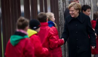 German Chancellor Angela Merkel shakes hands with children symbolizing so-called Mauerspechte (wall peckers - people who chipped the wall with hammers) along remains of the Berlin Wall at the Berlin Wall memorial site at Bernauer Strasse in Berlin, Germany, Sunday, Nov. 9, 2014. Twenty-five years ago - on Nov. 9, 1989 - the East-German government lifted travel restrictions and thousands of East Berliners had pushed their way past perplexed border guards to celebrate freedom with their brethren in the West. (AP Photo/Steffi Loos)