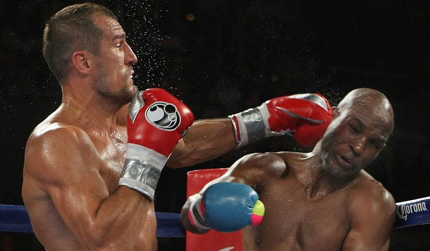 Bernard Hopkins of Philadelphia, PA, right, gets hit by Sergey Kovalev of Russia during the third round of the Main Event IBF, WBA and WBO Light Heavyweight Titles boxing in Atlantic City, N.J. on Saturday, Nov. 8, 2014. Kovalev won by TKO in the 12th round. (AP Photo/Tim Larsen)