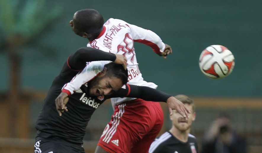 DC United's David Estrada, left, and  New York Bulls'  Bradley Wright-Phillips (99) battle for a head ball during the second half of the second match of their MLS soccer Eastern Conference semifinal playoff series, Saturday, Nov. 8, 2014, in Washington. The Red Bulls lost the game 2-1, but advanced 3-2 on aggregate after winning the first leg 2-0 last Sunday. (AP Photo/Luis M. Alvarez)