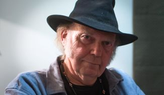 Canadian singer-songwriter Neil Young sits for a photograph during an interview with The Canadian Press before appearing with environmentalist David Suzuki at the final show on the Blue Dot Tour at the Orpheum Theatre in Vancouver, British Columbia, on Sunday Nov. 9, 2014. (AP Photo/The Canadian Press, Darryl Dyck)
