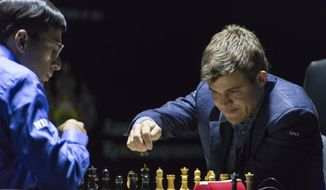Norway's Magnus Carlsen, currently the top ranked chess player in the world, right,  makes a move as he plays against India's former World Champion Vishwanathan Anand at the FIDE World Chess Championship Match in Sochi, Russia, Sunday, Nov. 9, 2014. (AP Photo/Artur Lebedev)