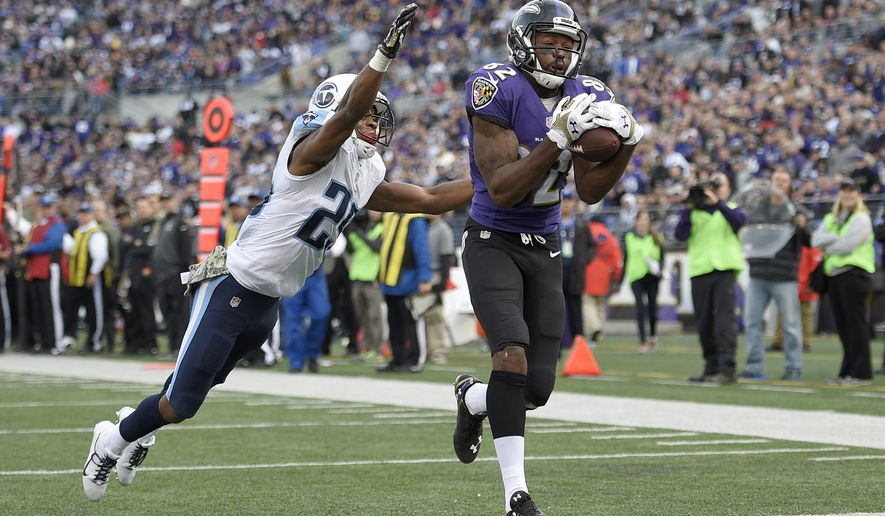 Baltimore Ravens wide receiver Torrey Smith (82) pulls in a touchdown pass under pressure from Tennessee Titans cornerback Blidi Wreh-Wilson (25) during the second half of an NFL football game in Baltimore, Sunday, Nov. 9, 2014. (AP Photo/Nick Wass)