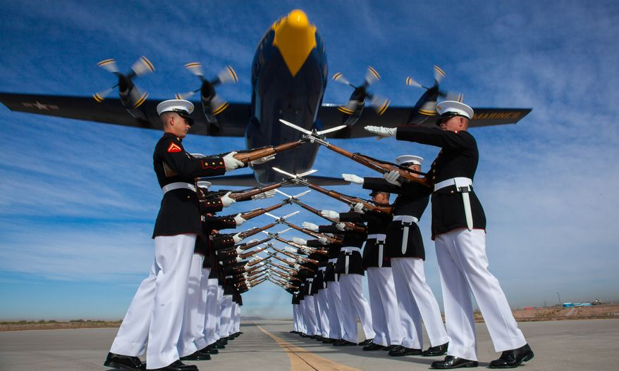 """The Blue Angels, Marine Corps' C-130 Hercules, affectionately known as """"Fat Albert,"""" flies over the Silent Drill Platoon at Marine Corps Air Station Yuma, Ariz., March 4."""