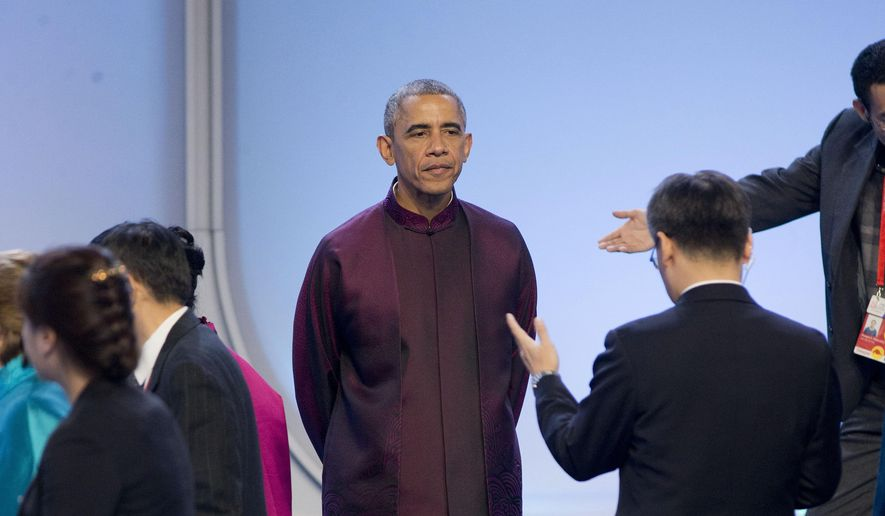 President Barack Obama takes his place on stage as he waits for other world leaders to arrive during the Asia-Pacific Economic Cooperation (APEC) Summit family photo, Monday, Nov. 10, 2014 in Beijing. Obama is in China to attend the Asia-Pacific Economic Cooperation (APEC) Summit. (AP Photo/Pablo Martinez Monsivais)