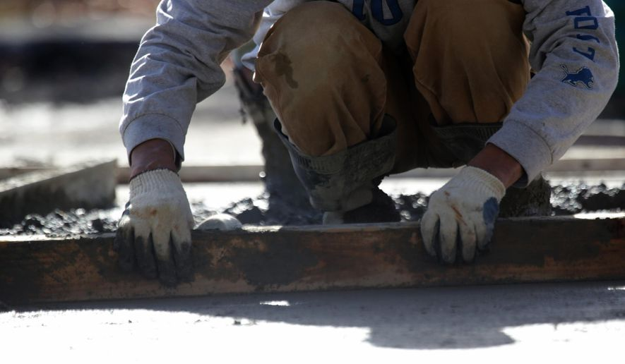 In a Friday, Nov. 7, 2014 photo, a worker smooths out the cement mix for the new playground being built at Burton Elementary School in Huntington Woods, Mich.  The school raised $460,000 to have it built and hoped the playground would be finished this week, but didn't plan on a cement shortage in Michigan. (AP Photo/Detroit Free Press, Kimberly P. Mitchell)  DETROIT NEWS OUT;  NO SALES