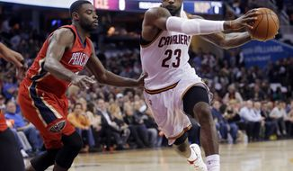 Cleveland Cavaliers' LeBron James (23) drives on New Orleans Pelicans' Tyreke Evans in the foist quarter of an NBA basketball game Monday, Nov. 10, 2014, in Cleveland. (AP Photo/Mark Duncan)