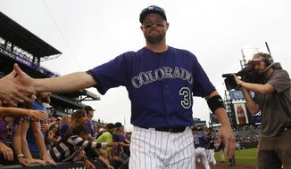 Fans congratulate Colorado Rockies' Michael Cuddyer as he walks around the field with teammates after the Rockies' 8-3 victory over the Arizona Diamondbacks in the Rockies' final home contest for the regular baseball game in Denver on Sunday, Sept. 21, 2014. (AP Photo/David Zalubowski)