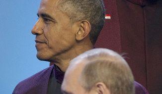 Russian President Vladimir Putin walks past U.S. President Barack Obama during the Aisa-Pacific Economic Cooperation (APEC) Summit family photo, Monday, Nov. 10, 2014 in Beijing. (AP Photo/Pablo Martinez Monsivais)