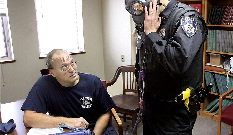 Alton, Ill., Fire Department engineer Bob Eichen, left, uses a machine to run a series of five tests on the gas mask of Alton Police officer Michael Beaber, right, at the Don Twichell Memorial Fire Station in Alton, Monday Nov. 10, 2014.  The Alton, Ill., Police Department has been preparing for any possible civil unrest or the need to assist other departments for over a month in advance of the verdict by the Grand Jury in the Ferguson, Mo., police shooting death of Michael Brown. (AP Photo/The Telegraph, John Badman) BELLEVILLE NEWS-DEMOCRAT OUT; ST. LOUIS POST-DISPATCH OUT