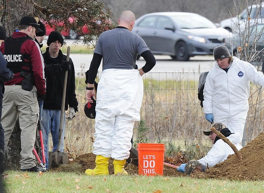 Members of law enforcement including Detroit police, dig, sift and using sub-surface imaging at the United Memorial Gardens cemetery, in Plymouth Township, Mich., Monday, Nov. 10, 2014. Authorities hoping to help close two cases from the 1980s are working to exhume two unidentified bodies at the cemetery. (AP Photo/Detroit News, Daniel Mears)