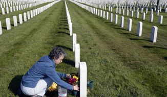 Darlene Angeli places flowers on the tombstone of her father, World War II veteran Eugen Angeli, who is buried alongside his wife Hazel, at Golden Gate National Cemetery on Monday, Nov. 10, 2014, in San Bruno, Calif. The U.S. celebrates Veterans Day Tuesday in honor of those who have served in the nation's military. (AP Photo/Marcio Jose Sanchez)