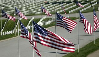 U.S. flags fly over war veterans' tombstones at Golden Gate National Cemetery on Monday, Nov. 10, 2014, in San Bruno, Calif. The U.S. celebrates Veterans Day Tuesday in honor of those who have served in the nation's military. (AP Photo/Marcio Jose Sanchez)