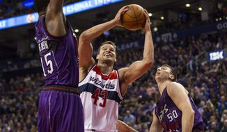Washington Wizards' Kris Humphries, center, shoots on Toronto Raptors' Patrick Patterson, left, and Tyler Hansbrough during the first half of an NBA basketball game Friday, Nov. 7, 2014, in Toronto. (AP Photo/The Canadian Press, Chris Young)