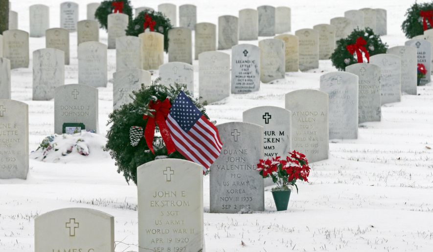 A flag stands with a wreath at a grave at Fort Snelling National Cemetery on Veterans Day, Tuesday, Nov. 11, 2014, in Minneapolis. (AP Photo/Jim Mone) ** FILE **