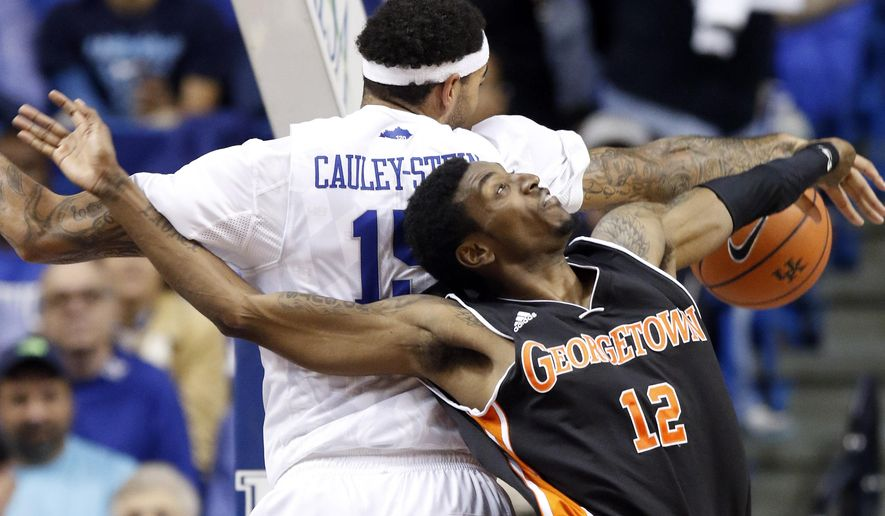 Kentucky's Willie Cauley-Stein, left, blocks the shot of Georgetown's Gerald Coleman during the second half of an NCAA college basketball exhibition game, Sunday, Nov. 9, 2014, in Lexington, Ky. Kentucky won 121-52. (AP Photo/James Crisp)