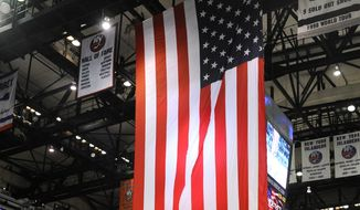 On Military Appreciation Night for Veteran's Day at the Nassau Coliseum, the 106th Rescue of the National Guard unfurled the United States flag during the singing to the National Anthem before the NHL hockey game between the New York Islanders and the Colorado Avalanche on Tuesday, Nov. 11, 2014, in Uniondale, N.Y. (AP Photo/Kathy Kmonicek)