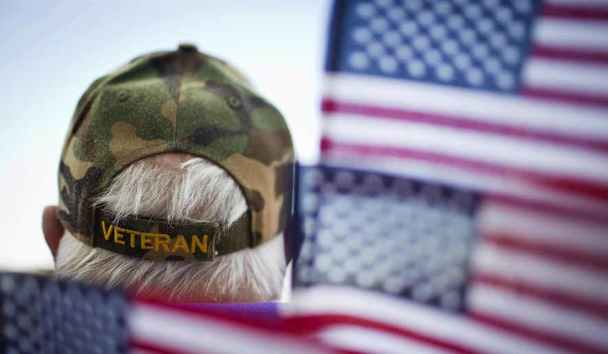 Frank Lindsey wears a veterans hat surrounded by flags as he attends a Veterans Day parade Tuesday, Nov. 11, 2014, in Montgomery, Ala. (AP Photo/Brynn Anderson) ** FILE **