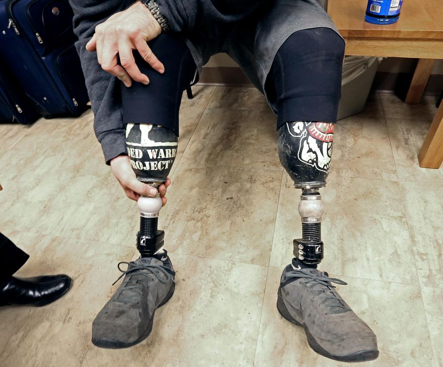 In this Monday, Nov. 10, 2014 photo, U. S. Marine Corps veteran Jake Janes positions one of his two prosthetic legs during an appointment to have one of the limbs repaired at Prosthetic Laboratories in Monona, Wisc. Janes, a Marine from Evansville, Wisc. who lost both legs below the knee in Afghanistan, goes hunting and fishing with his artificial legs. Improved prosthetics are helping Wisconsin veterans who lost limbs during tours in the Middle East maintain active lifestyles. (AP Photo/Wisconsin State Journal, John Hart)