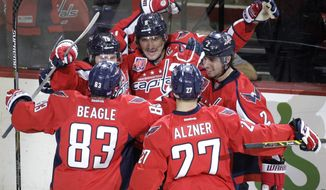 Washington Capitals' Alex Ovechkin, center, of Russia, celebrates with teammates Nicklas Backstrom, left,  of Sweden, Matt Niskanen (2),  Jay Beagle (83) and Karl Alzner (27) after scoring a goal during the first period of an NHL hockey game against the Columbus Blue Jackets, Tuesday, Nov. 11, 2014, in Washington. (AP Photo/Luis M. Alvarez)