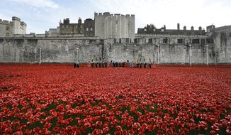 A remembrance day ceremony takes place at the near completed ceramic poppy art installation by artist Paul Cummins entitled 'Blood Swept Lands and Seas of Red' in the dry moat of the Tower of London in London, Tuesday, Nov. 11, 2014. The finished installation will be made up of 888,246 ceramic poppies, with the final poppy being placed on Armistice Day today. Each poppy represents a British and Commonwealth military fatality from World War I. (AP Photo/Kirsty Wigglesworth)