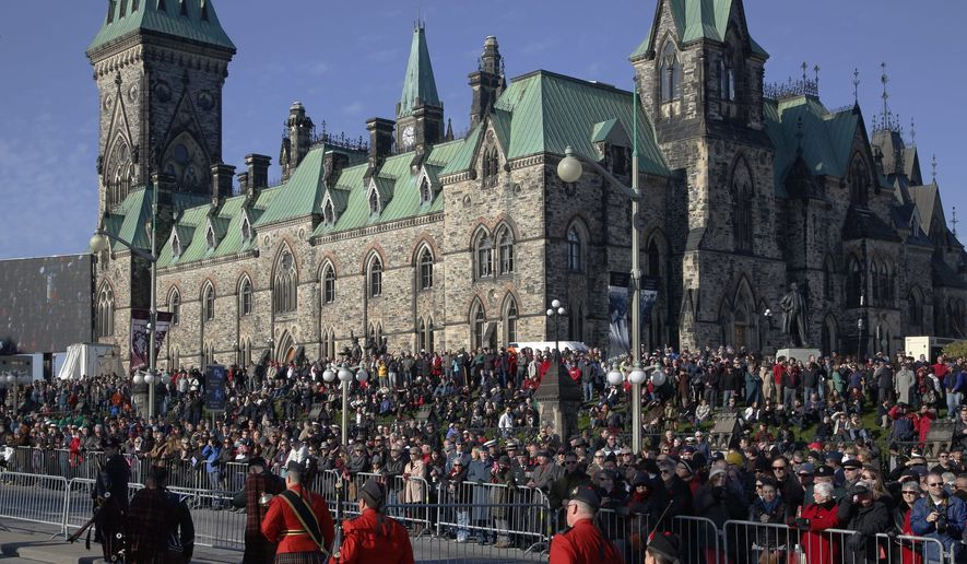 Crowds watch the Remembrance Day ceremony from Parliament Hill near the National War Memorial in Ottawa on Tuesday, Nov. 11, 2014.  (AP Photo/The Canadian Press, Patrick Doyle)