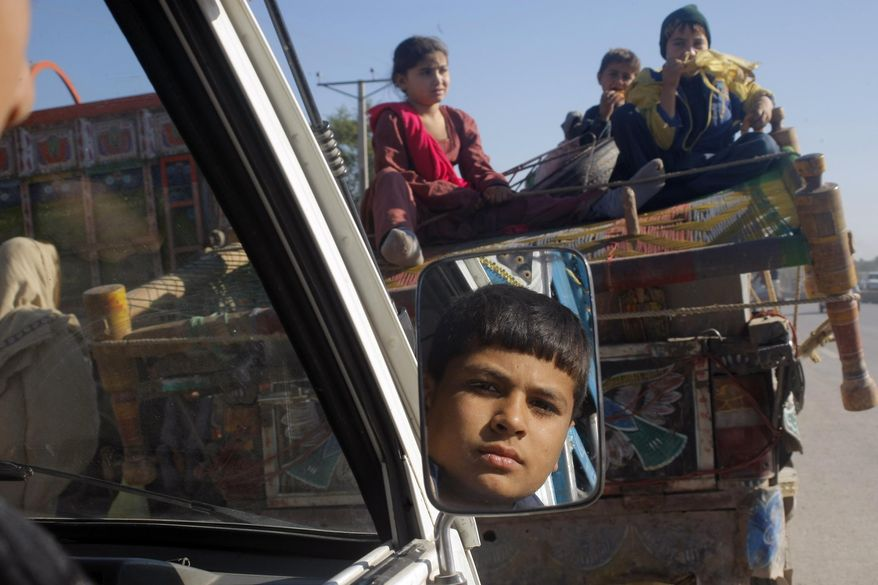Pakistani families fleeing fighting between security forces and militants in the neighboring Khyber tribal region arrive in Peshawar, Pakistan, Monday, Nov. 10, 2014. The Pakistani army is now regularly targeting militants' hideouts in Khyber, since fighters fled there from neighboring North Waziristan tribal region where it has been conducting a months long operation. (AP Photo/Mohammad Sajjad)