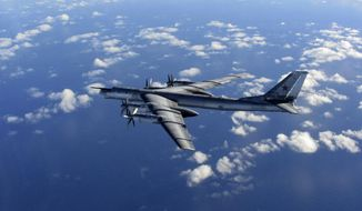 This is a Wednesday, Oct. 29, 2014, file photo provided by Britain's Royal Air Force of a Russian military long-range bomber aircraft photographed by an intercepting RAF quick reaction Typhoon (QRA) as it flies in international airspace. Russia's defense minister says the military will conduct regular long-range bomber patrols, ranging from the Arctic Ocean to the Caribbean and the Gulf of Mexico. (AP Photo/Royal AIr Force)