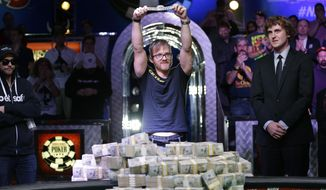 Martin Jacobson holds up the World Series of Poker main event bracelet after winning the tournament and its $10 million prize, Tuesday, Nov. 11, 2014, in Las Vegas. Ryan Riess, who won the tournament last year, is at right. (AP Photo/John Locher)
