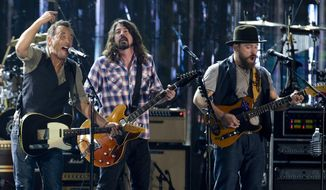 From left, Bruce Springsteen, Dave Grohl, and Zac Brown, sing on the National Mall in Washington, Tuesday, Nov. 11, 2014, during the Concert for Valor. The Veterans Day event is hosted by HBO, Starbucks and Chase and is free and open to the public. (AP Photo/Carolyn Kaster)