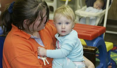 Tasha Burns holds her daughter, Heaven, 13 months, as her son, Brian, 4 months, sleeps at rear in a Salvation Army homeless shelter in Oklahoma City on April 3, 2007. The Burns family has been homeless since Hurricane Katrina hit Florida in August of 2005. (Associated Press) **FILE**