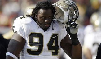 New Orleans Saints defensive end Charles Grant (94) takes his helmet off after coming out against the Washington Redskins during the first half of an NFL football game, Sunday, Dec. 6, 2009, in Landover, Md. (AP Photo/Rob Carr)
