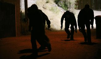 Four people sneak away from the US/Mexico border fence behind them after illegally crossing into the border town of Nogales, Arizona, on May 31, 2010. (Associated Press/Krista Kennell/Sipa Press) **FILE**