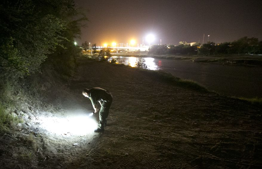 In this Wednesday, July 23, 2014 photo, a U.S. Border Patrol agent looks at fresh footprints as he searches the banks of the Rio Grande River in Roma, Texas for a person who crossed the river from Ciudad Miguel Aleman, Tamaulipas, Mexico. (AP Photo/Austin American-Statesman, Jay Janner)