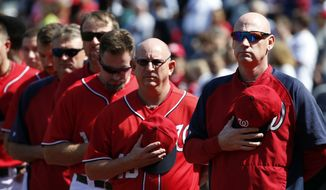 Washington Nationals manager Matt Williams, right, stands with his team during the National Anthem before the first baseball game of a doubleheader against the Miami Marlins at Nationals Park, Friday, Sept. 26, 2014, in Washington. (AP Photo/Alex Brandon)