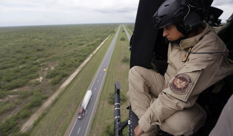 An U.S. Customs and Border Protection Air and Marine agent peers out of the open door of a helicopter during a patrol flight over McAllen, Texas, near the U.S.-Mexico border. (Associated Press)
