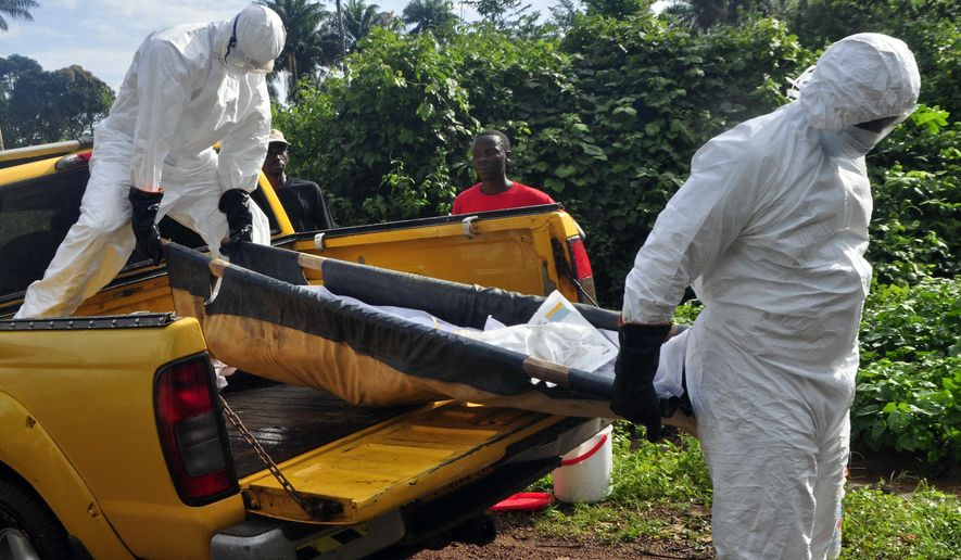 FILE - In this Oct. 27, 2014 file photo, health workers unload the lifeless body of a man suspected of contracting the Ebola virus, as they carry him to a grave site on the outskirts of Monrovia, Liberia. Health officials in the U.S. and Europe are scrambling to begin testing a handful of experimental Ebola drugs in Africa, but an ethical debate is brewing over how to appropriately test medicines amid an outbreak that has already killed nearly 5,000 people. (AP Photo/Abbas Dulleh, File)