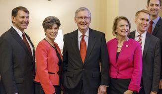 Senate Minority Leader Mitch McConnell of Ky., center, smiles as he welcomes some of the new GOP senators-elect in his office on Capitol Hill in Washington, Wednesday, Nov. 12, 2014. From left are, Sen.-elect Mike Rounds, R-S.D., Sen.-elect Joni Ernst, R-Iowa, Mitch McConnell, Sen.-elect Shelley Moore Capito, R-W.Va., Sen.-elect James Lankford, R-Okla., and Sen.-elect Tom Cotton, R-Ark. (AP Photo/J. Scott Applewhite)