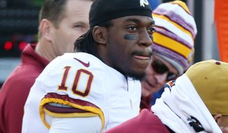 Washington Redskins quarterback Robert Griffin III (10) sits on the bench while the Minnesota Vikings have the ball during the second half of an NFL football game, Sunday, Nov. 2, 2014, in Minneapolis. (AP Photo/Jim Mone)
