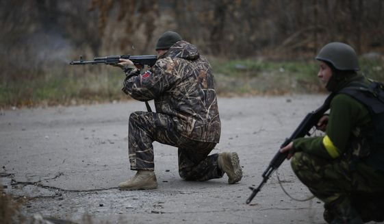 Ukrainian volunteer fighters shoot in the village of Peski near Donetsk, eastern Ukraine, Wednesday, Nov. 12, 2014. Fighting has continued in the east despite a cease-fire agreement between Ukraine and the rebels signed in September. Ukraine and the West accused Russia recently of sending in new troops and weapons.  (AP Photo/Maxim Vetrov)